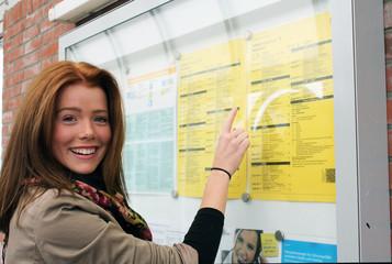 junge Frau vor einem Fahrplan