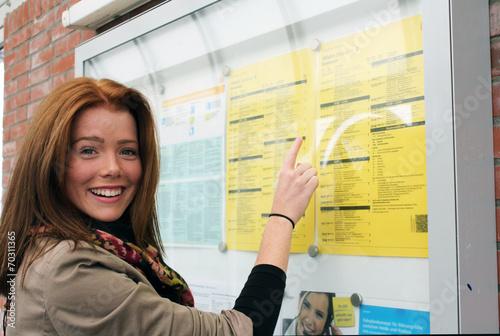 Leinwanddruck Bild junge Frau vor einem Fahrplan
