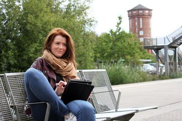 freundliche Frau sitzt mit Tablet auf dem Bahnsteig