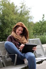 junge Frau freut sich unterwegs über Nachricht