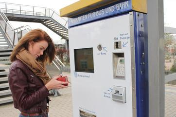 junge Frau am Fahrkartenautomat