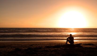 Surfer sitting on a calm ocean beach with surf board
