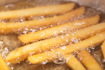 French fries in hot fat (close up shot)
