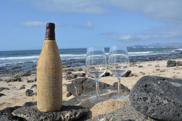 Two Wine Glasses And Bottle On The Beach With Sea Background