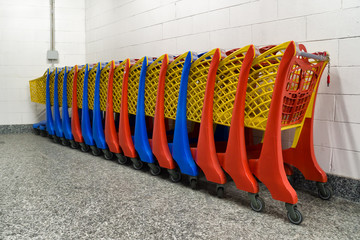 row of colorful shopping trolley in supermarket