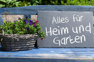 Blaue Bank in Garten vor Steinmauer mit Schiefertafel