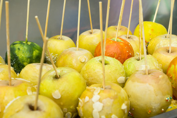 With sugar-coated apples on a stick