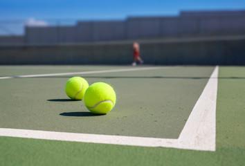 two tennis ball near baseline
