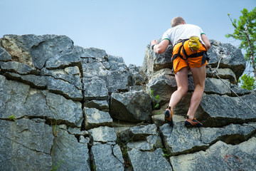 Climber climbing on top of a mountain with a safety rope