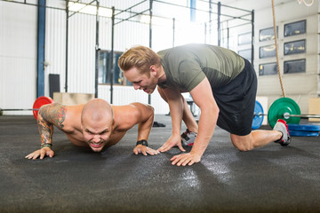 Trainer Motivating Man In Doing Pushups