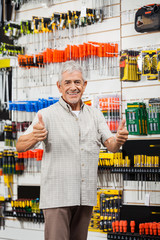 Customer Gesturing Thumbs Up In Hardware Shop