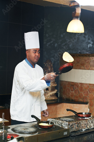 Foto op Canvas Pizzeria chef juggling with pancake on pan