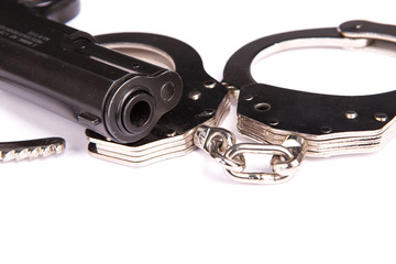 police handcuffs with a gun isolated on a white background