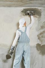 Plasterer at indoor wall work