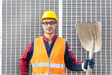 portrait of a young engineer wearing a helmet against metal back