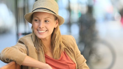 Portrait of smiling woman sitting on public bench