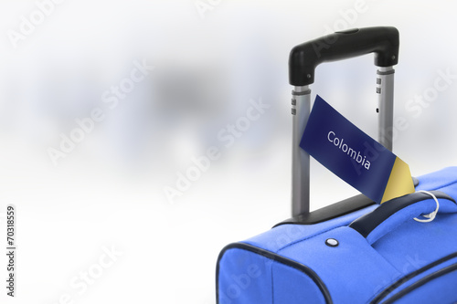 canvas print picture Colombia. Blue suitcase with label at airport.