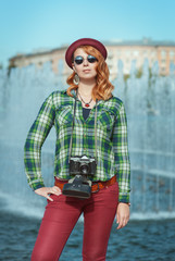 Hipster woman in hat and glasses with retro camera