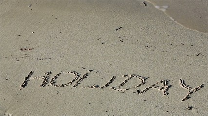 holiday sign in sand on beach