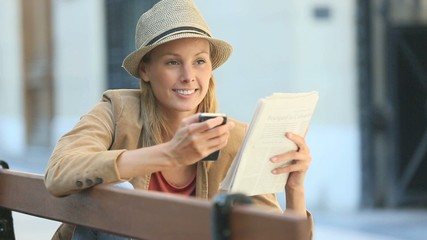 Smiling woman reading newspaper on public bench