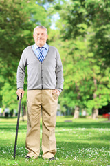 Senior man walking with a cane in park
