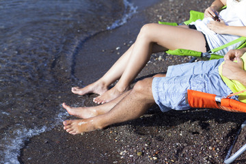 Young couple is sitting on chaise lounge at the beach