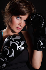 Portrait of a beautiful woman wearing boxing gloves