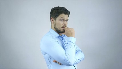 Portrait of a young pensive businessman looking at camera.