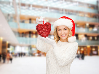 smiling woman in santa helper hat with red heart