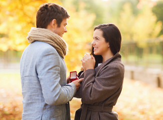 smiling couple with red gift box in autumn park