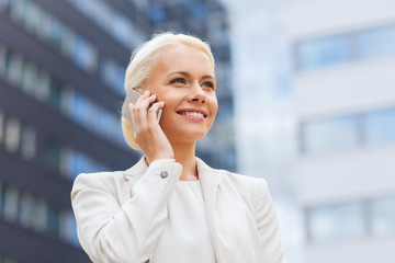 smiling businesswoman with smartphone outdoors