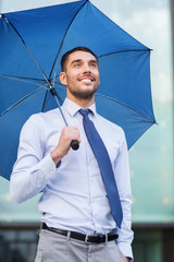young smiling businessman with umbrella outdoors