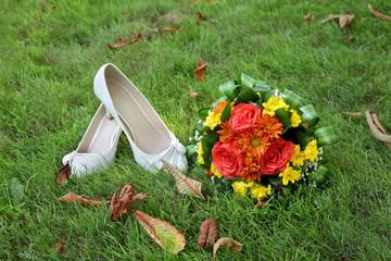 Wedding accessories, bride shoes, bouquet at grass