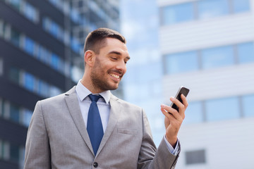 smiling businessman with smartphone outdoors