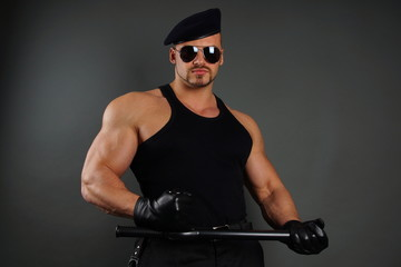 Muscular soldier in leather gloves poses with nightstick