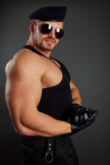 Muscular soldier in leather gloves shows his biceps