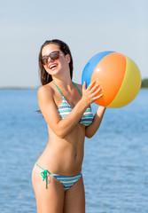 smiling teenage girl sunglasses with ball on beach