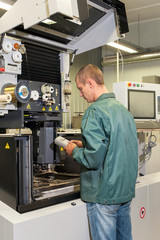 Worker operating industrial cnc machine in workshop.