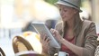 Girl at coffee shop using tablet and reading newspaper