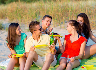 smiling friends sitting on summer beach