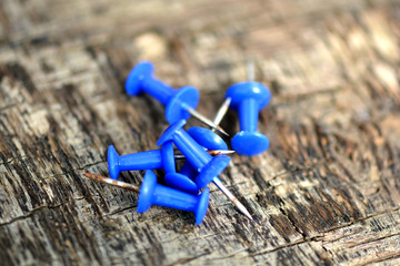 blue push pins on old wooden background
