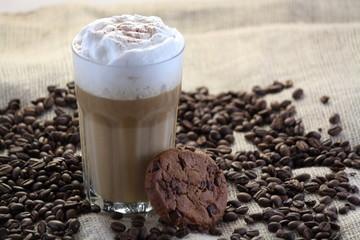 Latte Macchiato mit Keks und Kaffeebohnen