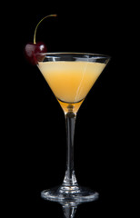 Yellow cocktail decorated with cherry in martini cocktails glass