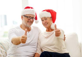 happy senior couple in santa helper hats at home