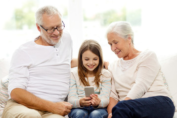 smiling family with smartphone at home