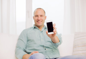 close up of smiling man with smartphone at home