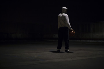 Portrait of a hooded basketball player holding a ball at night
