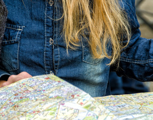 Couple checking city map outdoor. Detail on hands