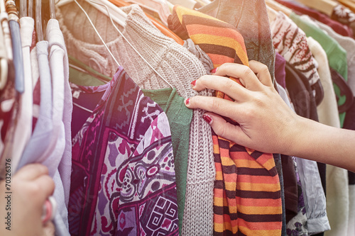 close up of a hand, looking on a flea market for clothes - 70326376