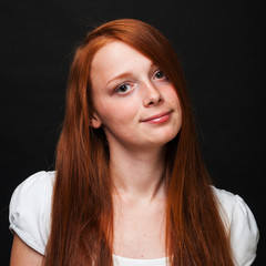Red-haired girl on dark background in  white T-shirt